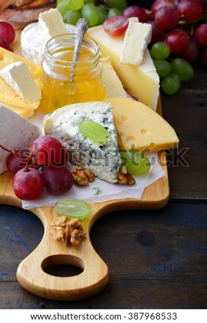 Various types of fresh Cheeses on cutting board on old table - stock photo