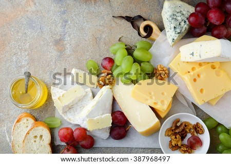 Various types of fresh Cheeses with grapes, honey, bread and walnuts on slate background. Top view - stock photo