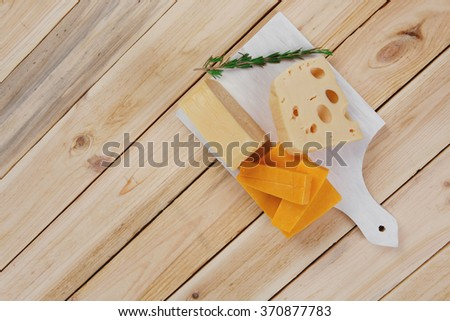 various types of fresh raw aged delicatessen cheese on white plate over light wooden table cheddar edam swiss - stock photo