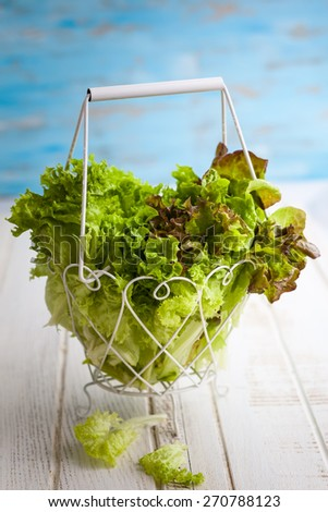 Various types of lettuce in a basket on the wooden table - stock photo