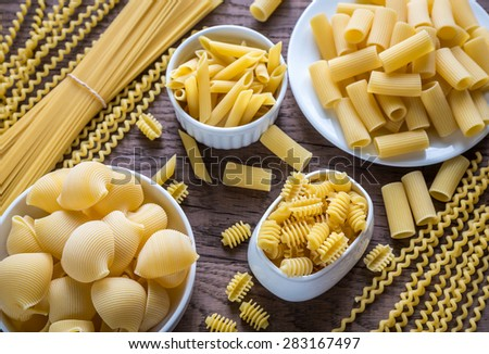 Various types of pasta on the wooden background - stock photo