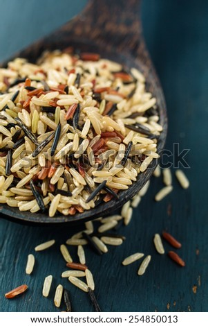 Various types of rice on old spoon, close-up - stock photo