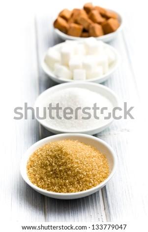 various types of sugar in ceramic bowls - stock photo