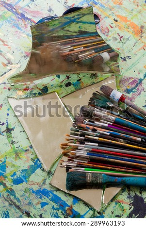 various used brush on the painting table with mirror - stock photo