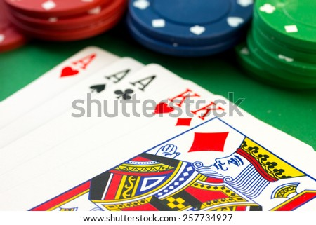 Various value poker chips on background showing a poker hand of a full house kings over aces. - stock photo