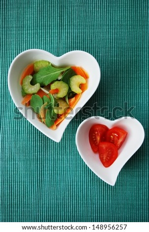 Various vegetables salad in two heart shape bowls on green background - stock photo