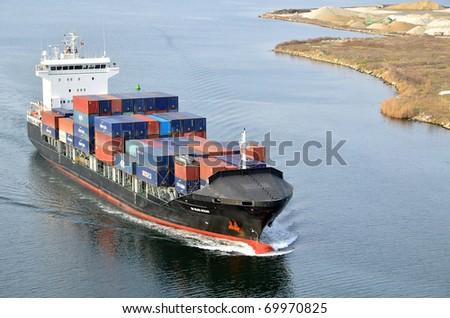 VARNA, BULGARIA - JANUARY 20: Cargo ship DS BLUE OCEAN (Flag: United Kingdom, IMO: 9341976) sails into open sea on January 20, 2011 in Varna, Bulgaria. Ship`s next destination is Island of Malta. - stock photo