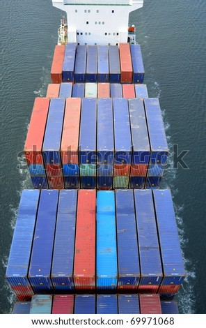 VARNA, BULGARIA - JANUARY 20: Cargo ship DS BLUE OCEAN (Flag: United Kingdom, IMO: 9341976) sails into open sea on January 20, 2011 in Varna, Bulgaria. Containers on board the ship seen from above. - stock photo