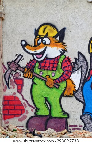Varna, Bulgaria - May 2, 2015: Street art by unknown artist. A cartoon of fox and wolf doing demolition job on a construction site.  - stock photo
