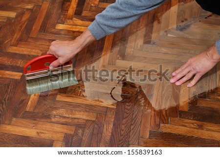 Varnishing of oak parquet floor, workers hand and brush - stock photo