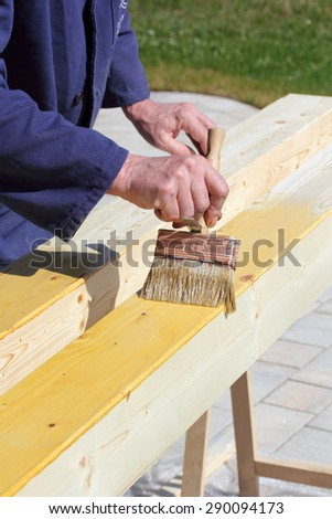 Varnishing of pine wooden beams - stock photo