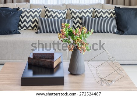 vase of flower with books on wooden table in living room at home - stock photo