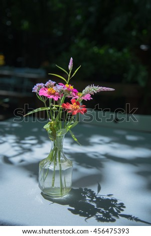Vase of flowers on a white table. - stock photo