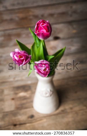Vase of natural tulips. flowers on a wooden background - stock photo