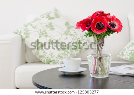 vase of red flowers in modern white living room - home decor - stock photo