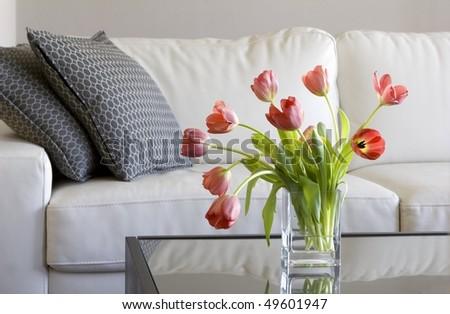 vase of red tulips in modern white living room - home decor - stock photo