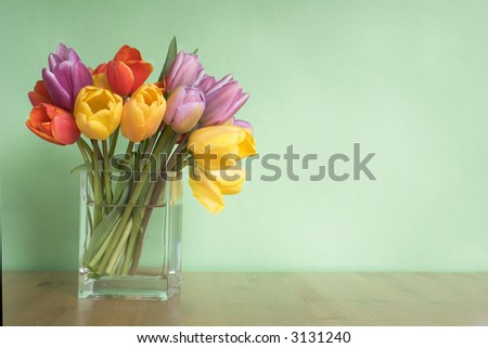 vase of tulips on table - green background - copy space - stock photo