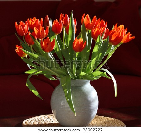 Vase with Orange Tulips in Modern Interior. Crackle-glazed vase, round place-mat of water hyacinth; background of burgundy-red sofa. - stock photo
