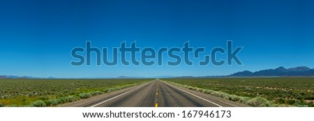 Vast endless stretch of open road in western America carries on into the distance. - stock photo