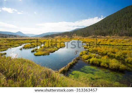 Vast landscape in the mountains showing fall colors of blue, orange, yellow, and green. - stock photo