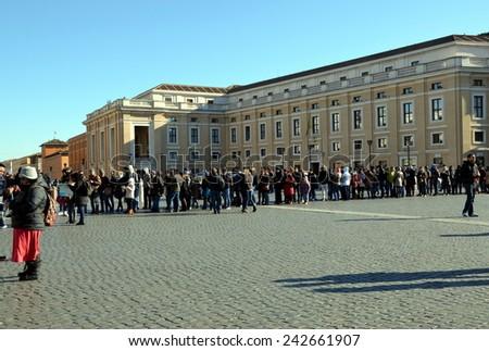 VATICAN CITY, VATICAN - DEC 29, 2014 - Tourists in long line at Saint Peter's Square in Vatican City, Vatican. Saint Peter's Square is among most popular pilgrimage sites for Roman Catholics - stock photo