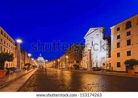 vatican italy rome street cobblestone leading to st peter's cathedral at sunrise illuminated street lamps and ancient houses on sides as landmark - stock photo