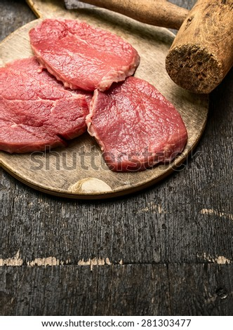 Veal schnitzel preparation on rustic wooden background with old meat hammer - stock photo