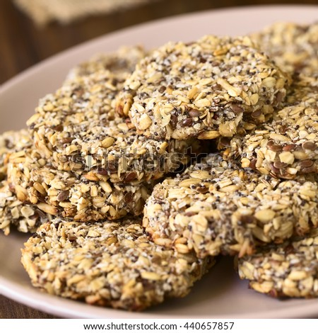 Vegan cookies made of banana, oatmeal, roasted oat grains, linseed, poppy seeds, grated coconut, chia seeds, photographed with natural light (Selective Focus, Focus on the front of the top cookie) - stock photo