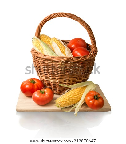 Vegan home kitchen still life of healthy diet products. Ripe golden corn cobs and large red salad tomatoes in old wicker basket on chopping wooden board isolated on white backdrop with clipping mask - stock photo