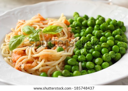 Vegan meal. Pasta with tomato sauce and green peas - stock photo