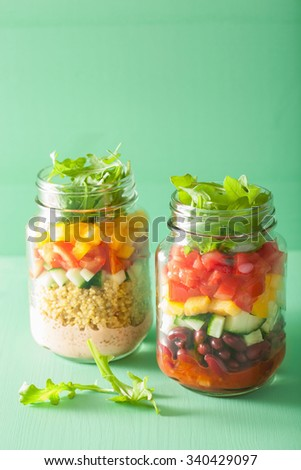 vegan quinoa bean vegetable salad in mason jars - stock photo