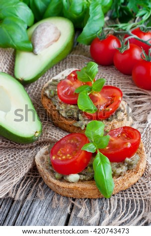 Vegan sandwich with avocado and vegetables on wooden background  - stock photo