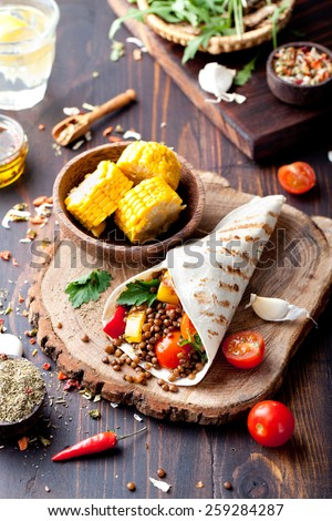 Vegan tortilla wrap, roll with grilled vegetabes and lentil  and boiled corn cob on a wooden background - stock photo