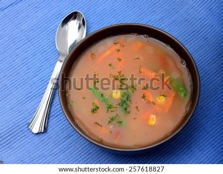 Vegan vegetable broth soup on blue placemat - stock photo