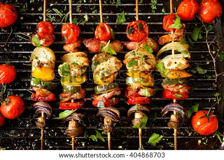Vegetable and meat skewers in a herb marinade on a grill pan - stock photo