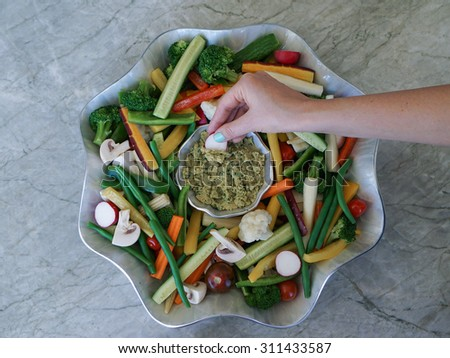 Vegetable Crudites and Dip/ vegetable platter, healthy eating, concept/ hand reaching for a piece of vegetable - stock photo