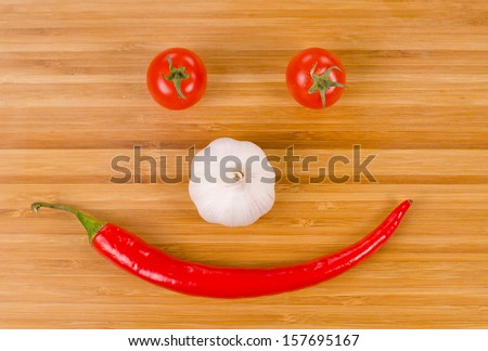 Vegetable face formed from a whole fresh red hot chilli pepper for a mouth, bulb of garlic for a nose and ripe red cherry tomatoes for eyes in a fun food background - stock photo