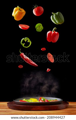 Vegetable falling into a hot cast iron pan - stock photo