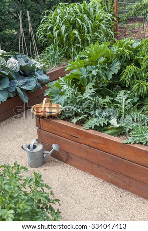 Vegetable garden beds with trug and watering can - stock photo