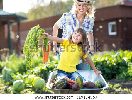 Vegetable garden - child and mother gardeners with carrots and other vegeatbles - stock photo