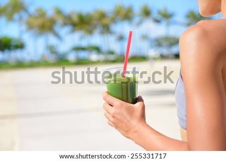 Vegetable green detox cleanse smoothie - Woman drinking after fitness running workout on summer day. Girl drinking green juice or smoothie in fitness and healthy lifestyle concept.  - stock photo