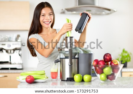 Vegetable juice raw food - healthy eating woman with juicer juicing green vegetables and apple fruits as part of her wellness food. Beautiful happy mixed Asian woman with juice maker in kitchen. - stock photo