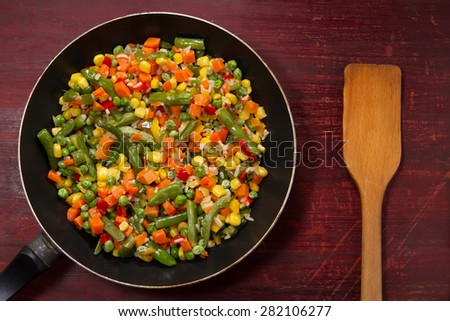 vegetable mix in the pan on wooden background - stock photo