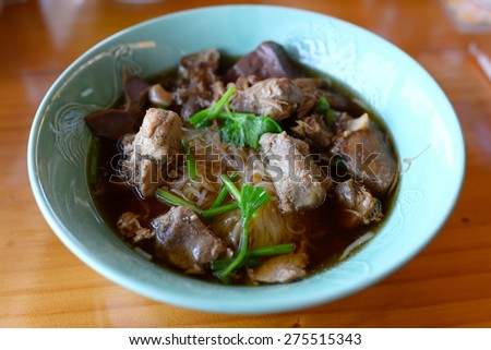 Vegetable noodle with stewed pork on wood table - stock photo