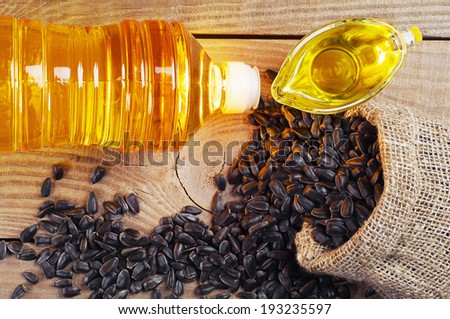 Vegetable oil and sunflower seeds in shack on wooden table. Top view - stock photo