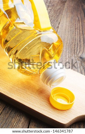 Vegetable oil in plastic bottle closeup on a cutting board - stock photo