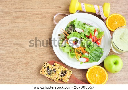 Vegetable salad,cereal cracker,fruits and dumbbell.Health and diet concept - stock photo