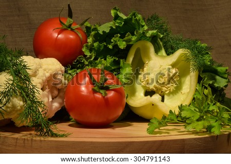 Vegetable set of white pepper, two red tomatoes, salad leafs, parsley and dill branches laid pretty on the table  - stock photo