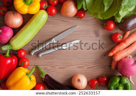 Vegetable set with knifes: ripe tomatoes, paprika, zucchini and an eggplant on a wooden background with a copy space in the center. Top view - stock photo