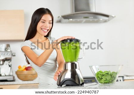 Vegetable smoothie woman blending green smoothies with blender home in kitchen. Healthy eating lifestyle concept portrait of beautiful young woman preparing drink with spinach, carrots, celery etc. - stock photo